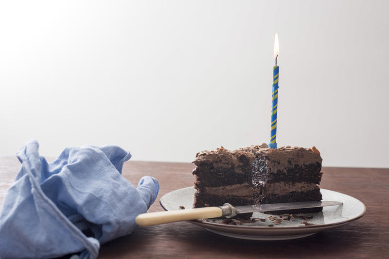 Chocolate birthday cake with burning blue candle on a plate on a table with matching blue napkin viewed low angle