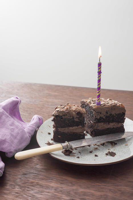 Sliced remains of a chocolate birthday cake with burning candle on a plate on a wooden table with a knife and copy space