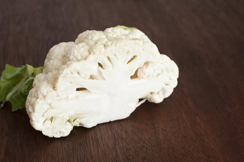 A close up of a halved cauliflower head on a timber bench.