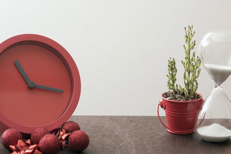 Christmas countdown wit festive red clock surrounded by decorations on a wooden table with hourglass