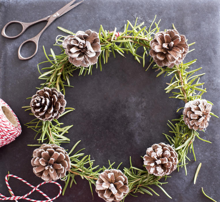 Handmade Christmas crafts with pine wreath with fresh green foliage and cones alongside scissors and twine