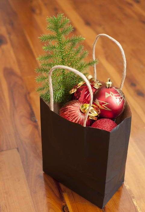 Paper bag filled with colorful red Christmas decorations and a small tree to decorate the house interior over the holiday season