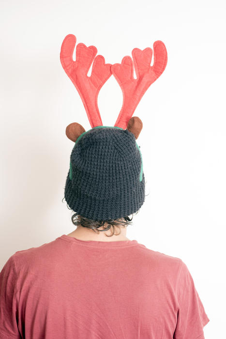 Person wearing a red Christmas reindeer hat with antlers viewed from the rear over white