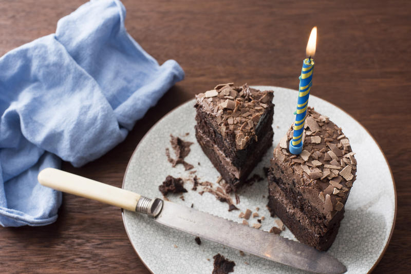 Cut iced chocolate birthday cake with single burning blue candle and matching napkin on a wooden table