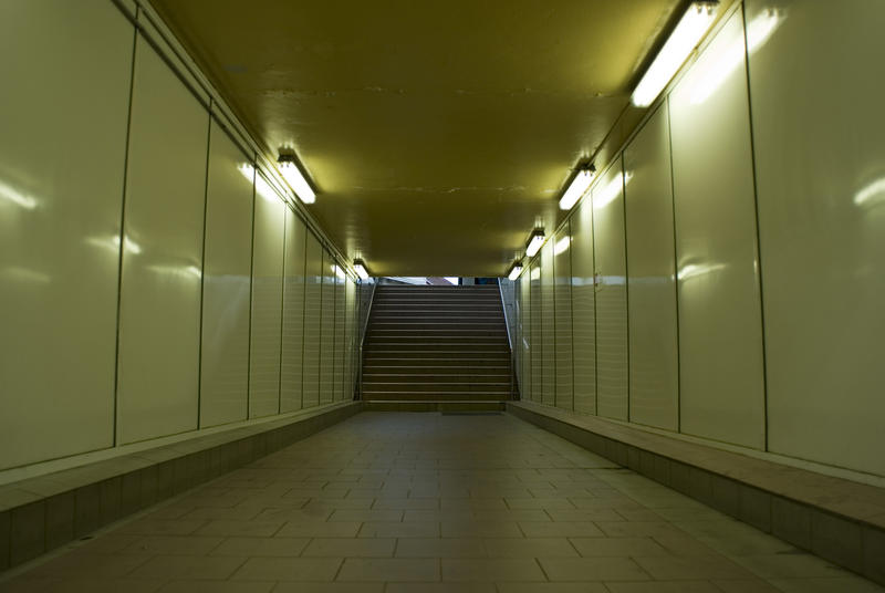 Empty illuminated underground subway tunnel with steps at the end in a concept of the travel ban during the coronavirus pandemic