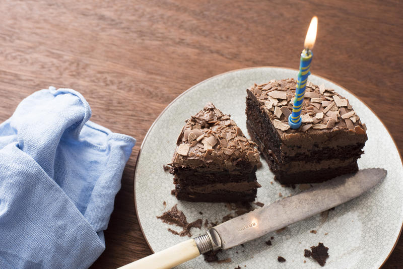 Remaining slices of a chocolate birthday cake with burning blue candle on a white plate with knife on a wooden table