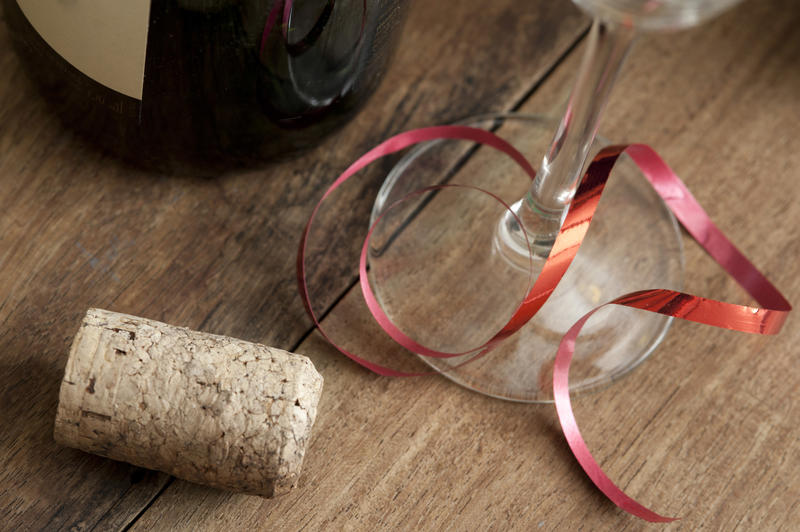 Party background concept with cork and glass tied with a festive red ribbon alongside a bottle of wine pr champagne