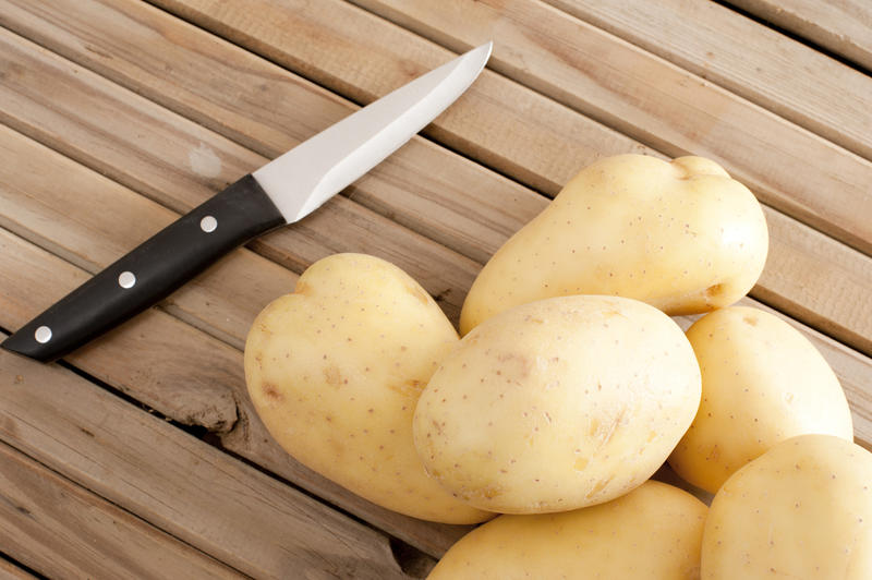 A close up of white potatoes and a sharp knife on a timber slatted bench.