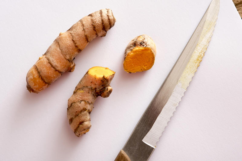 A close up of sliced turmeric and a serrated knife on a white chopping board.