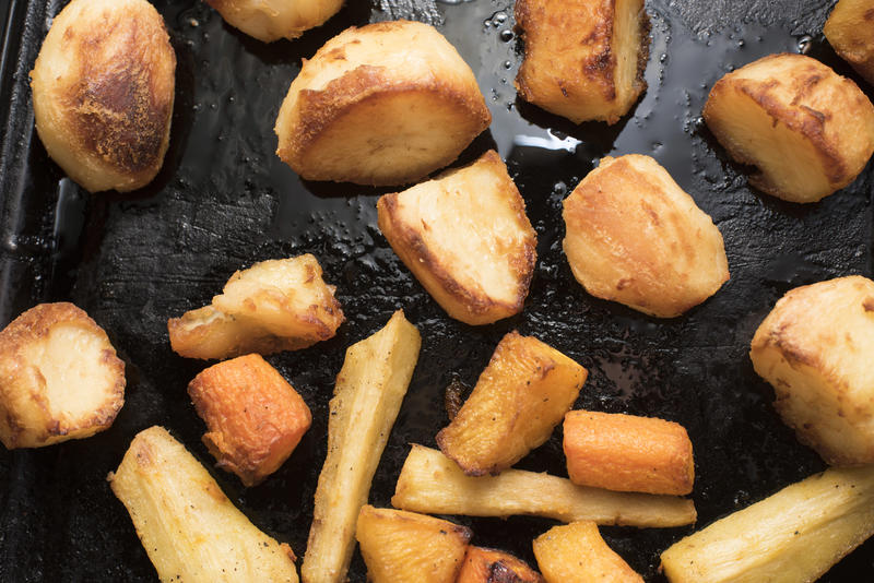 Roasting potatoes and vegetables with oil on black pan, viewed in close-up from above