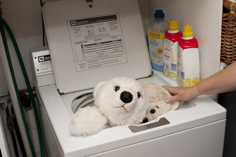Person sanitizing plush stuffed kids toys in a washing machine in a concept of infection control during the coronavirus pandemic