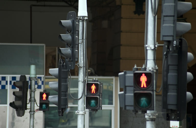 Covid Lockdown Concept: Traffic lights at a street intersection showing the red man pedestrian sign forbidding a crossing by people against a city background