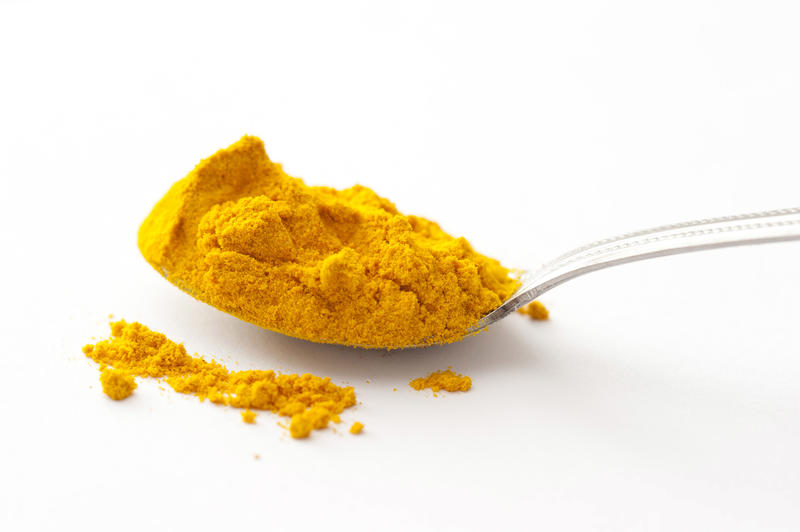 Full spoon of yellow turmeric powder spice viewed from the side in close-up on white surface