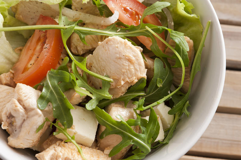 Healthy warm chicken salad topped with rocket and sliced tomatoes in a close up view in a bowl