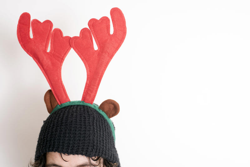 Person wearing a pair of festive red reindeer antlers to celebrate Christmas on a knitted hat in close up with copy space