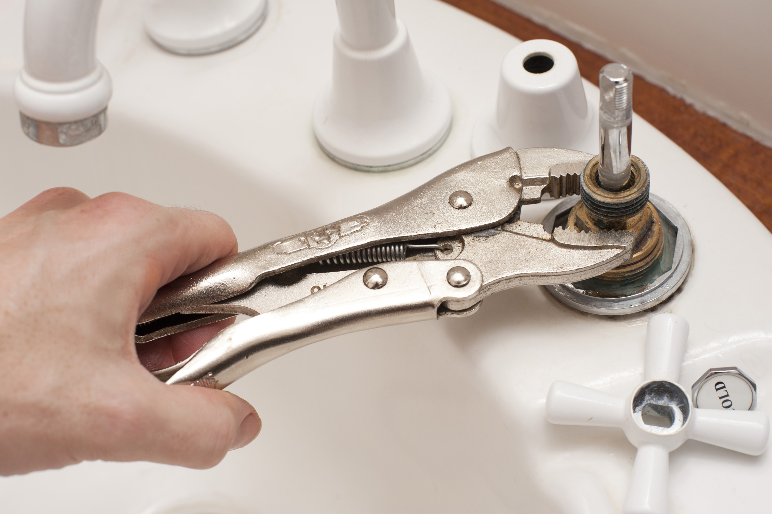 Nice Man Repairing A Broken Faucet Or Tap On A Bathroom Sink Using A Mole Grip  Pliers