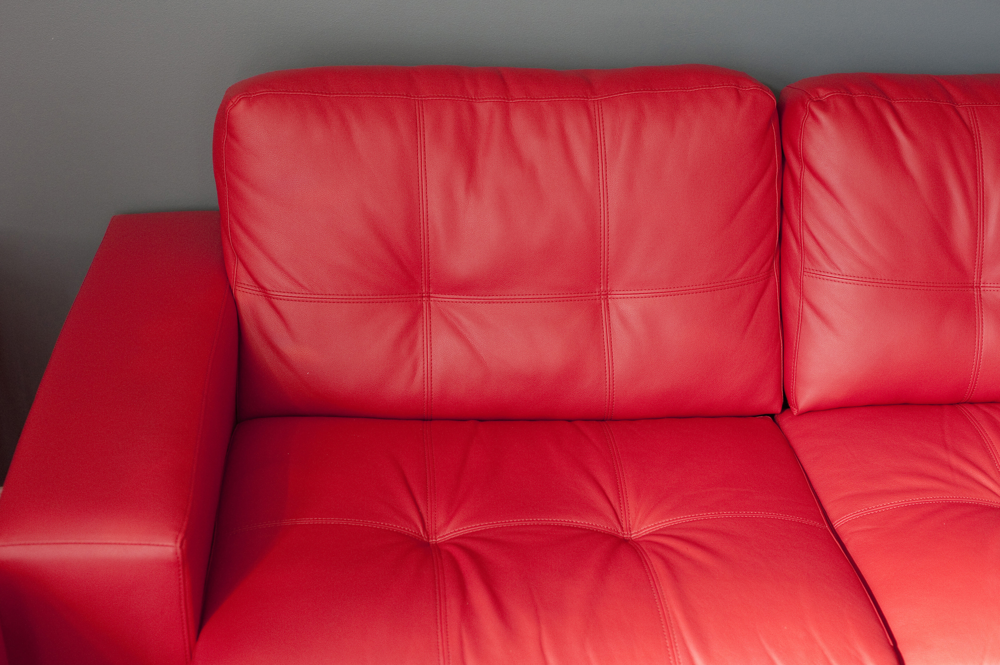close up elegant glossy red leather sofa in front a gray wall at the living room