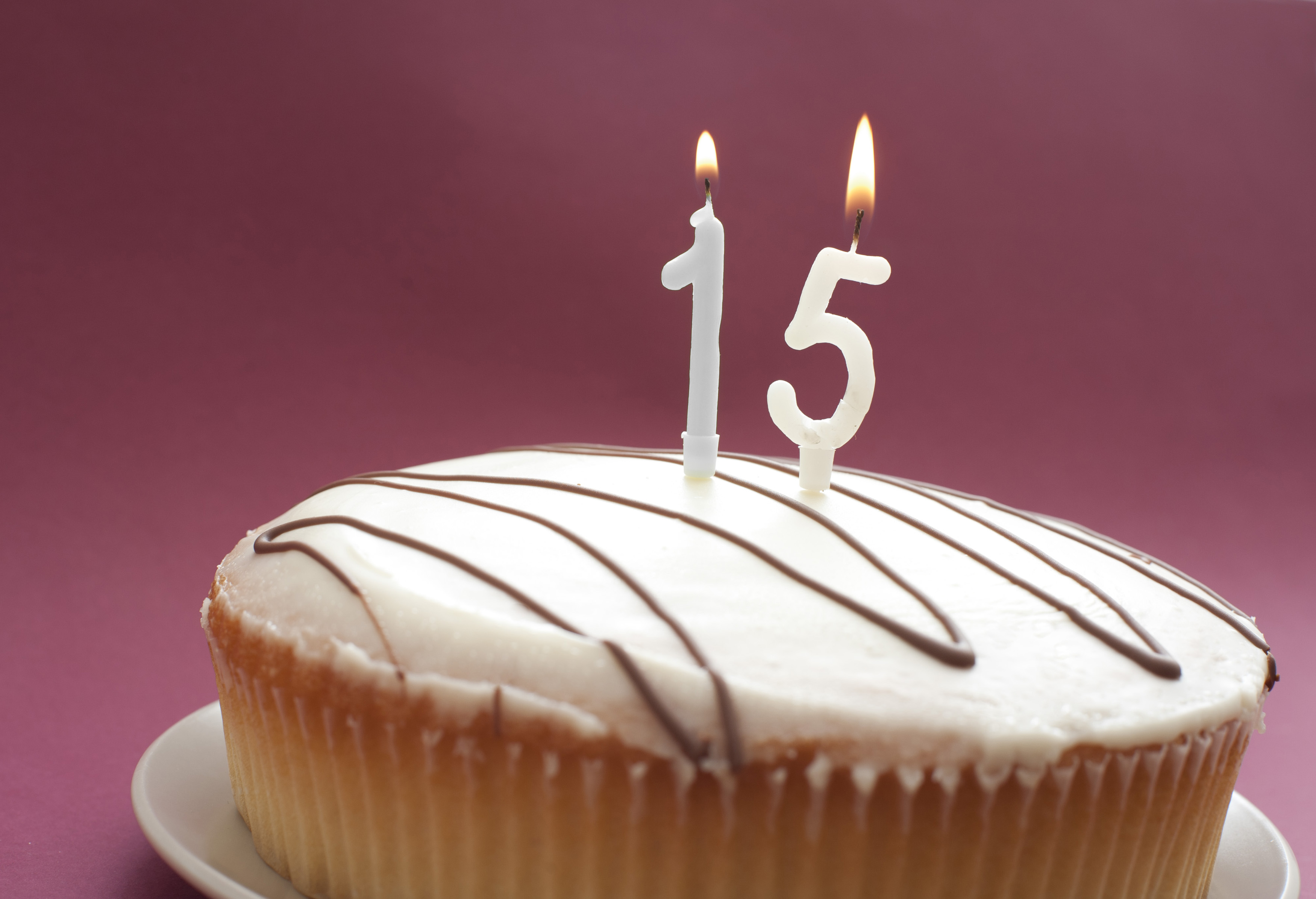 Iced 15th Birthday Cake With Burning Number Candles Over A Pink Background Copyspace For Your