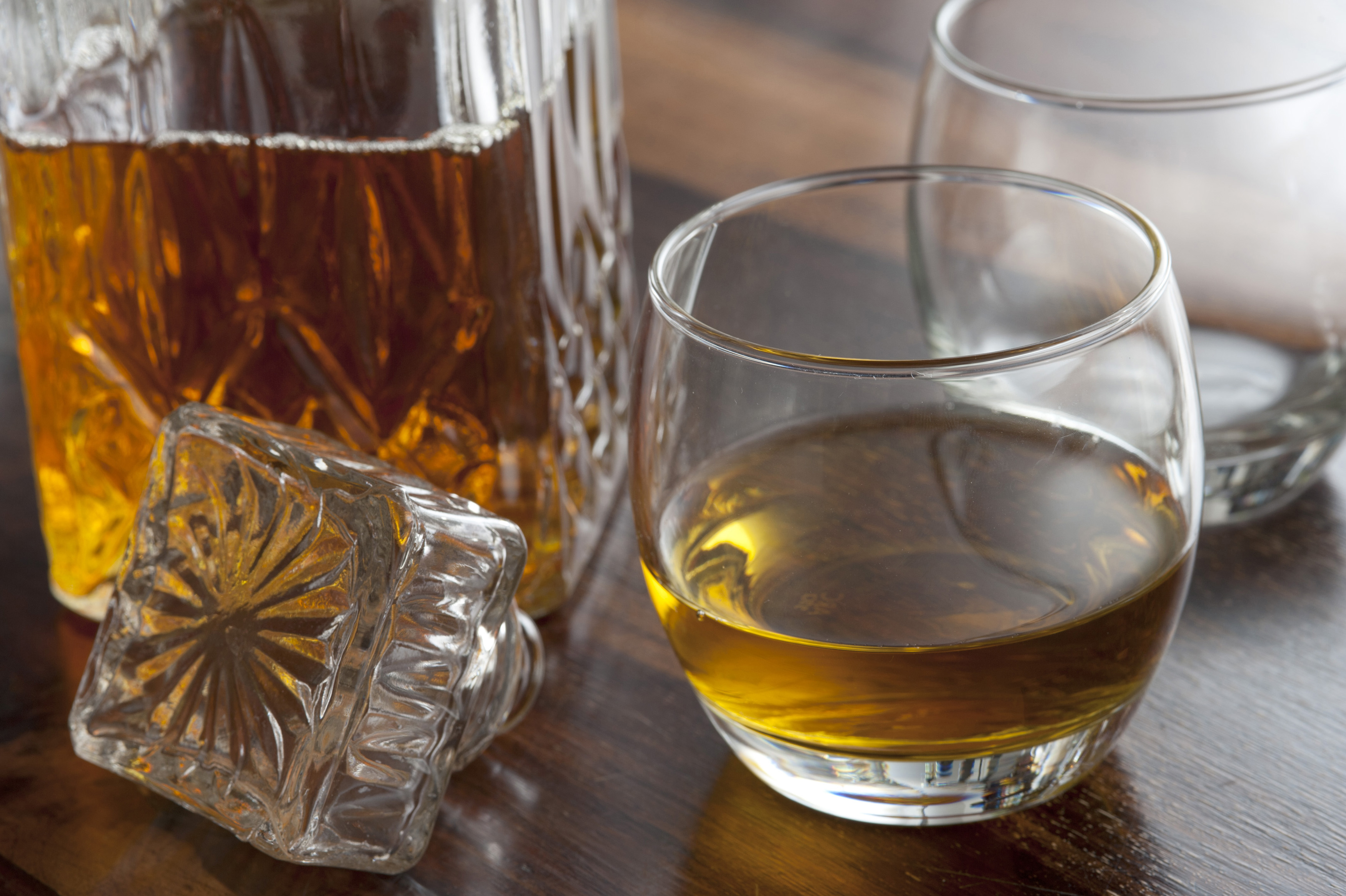 A Whiskey Glass And Decanter Stopper On A Wooden Table
