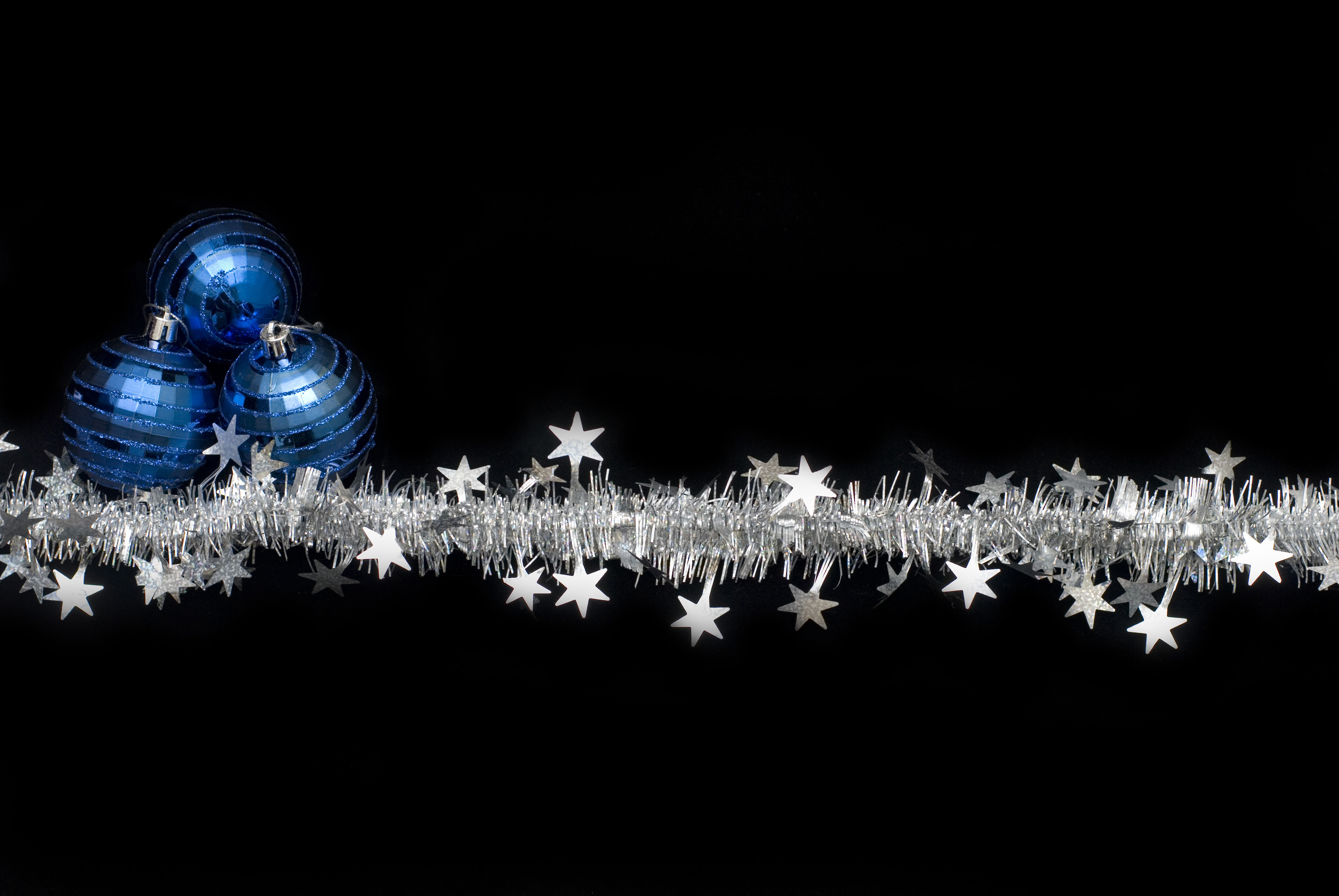 A String Of Silver Tinsel With Three Red Christmas Balls On Black Background