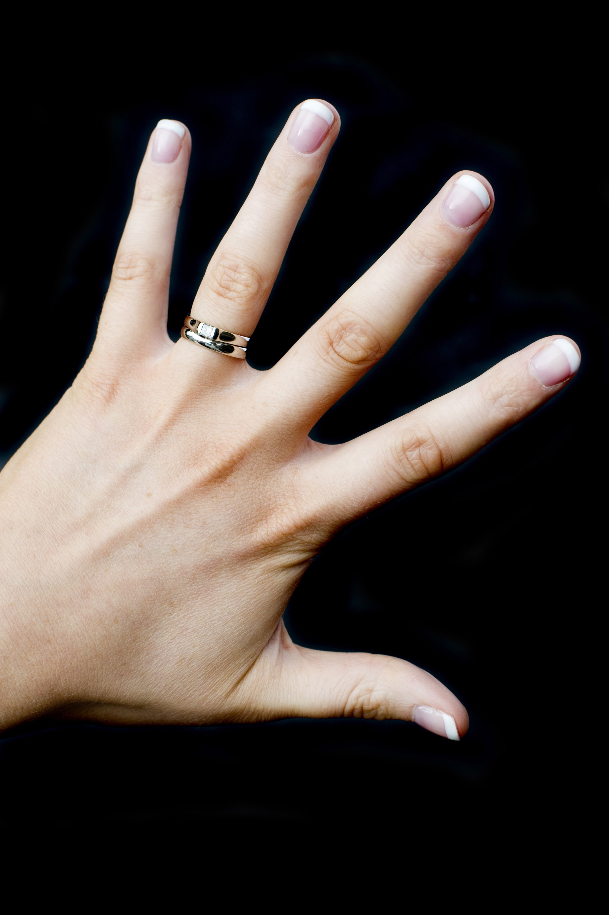 Cut Out On A Black Background, A Young Woman Wearing Wedding And Engagement  Rings