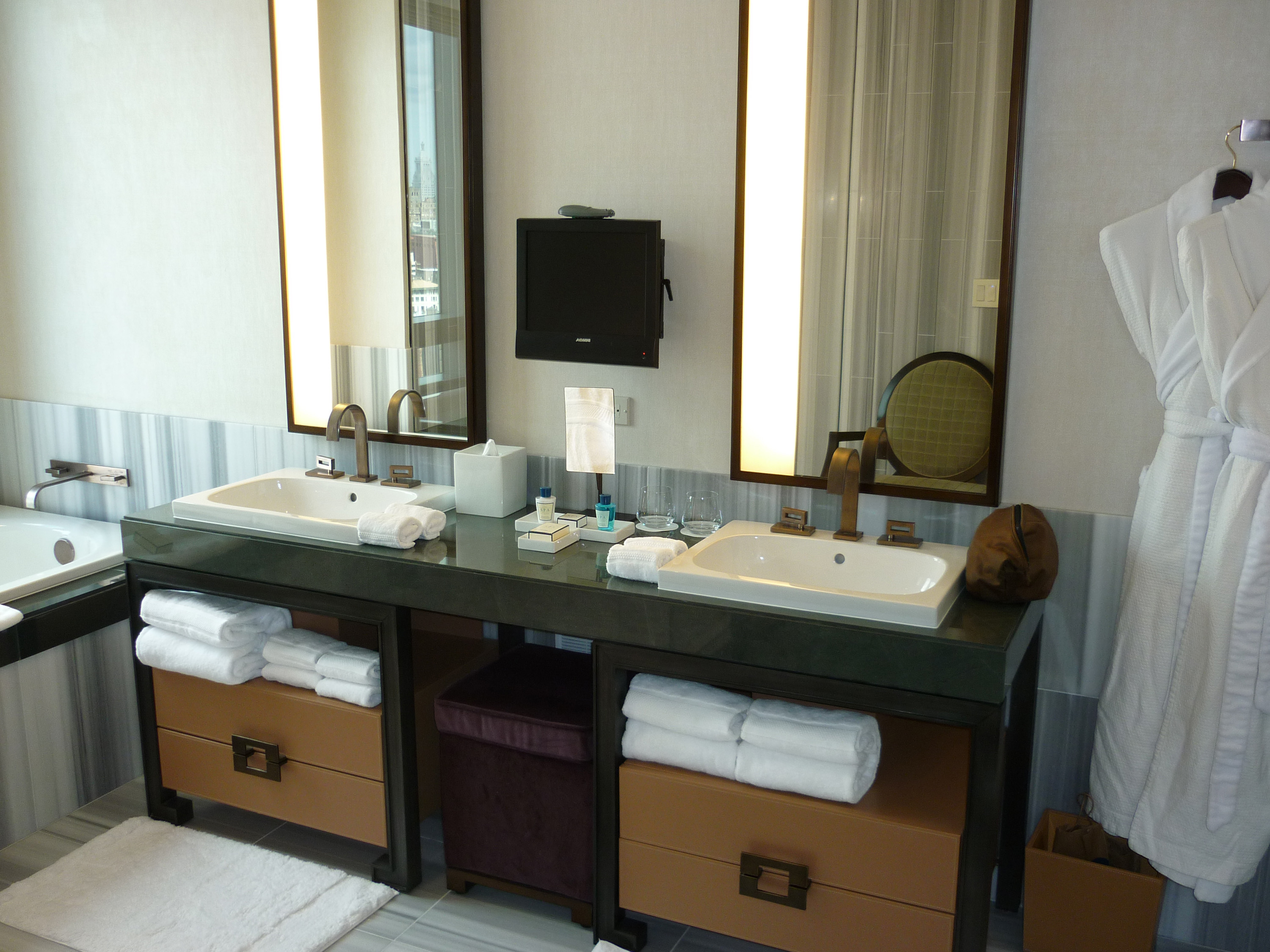 Fancy Luxury bathroom interior with a double vanity and soft fluffy white towels and a robe