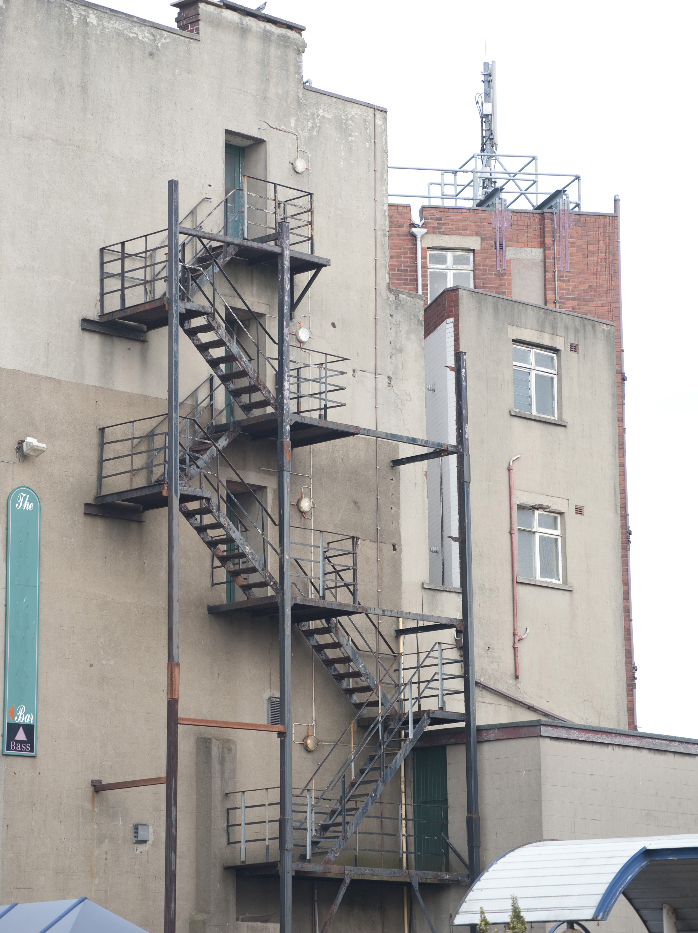 Metal Fire Escape On The Outside Wall Of An Urban Building Providing An Emergency  Exit In