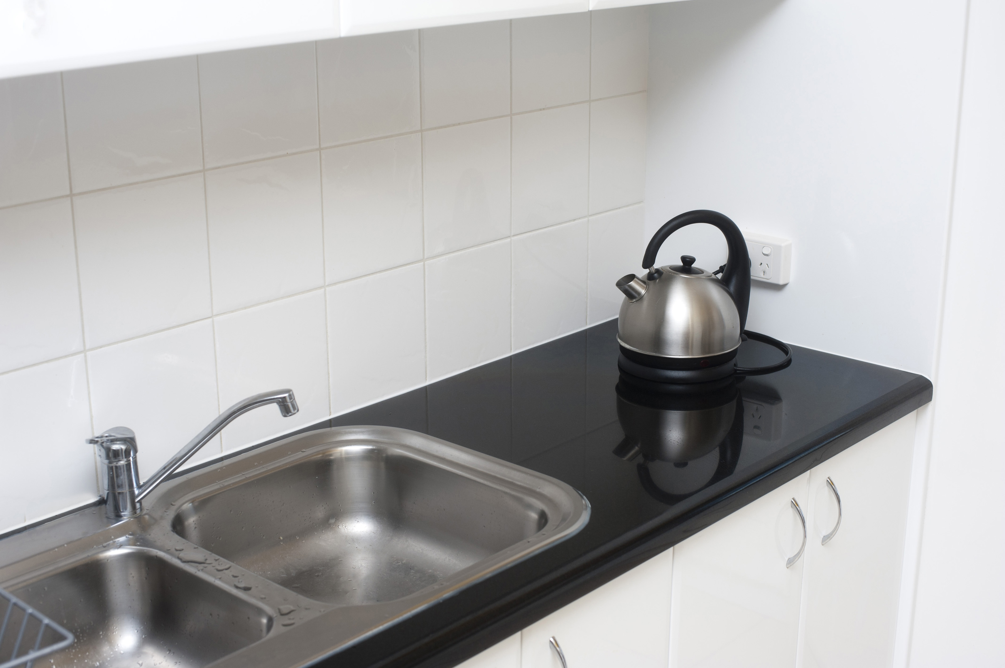 Small kitchen with double stainless steel sink unit, black countertop and  white tiles as a