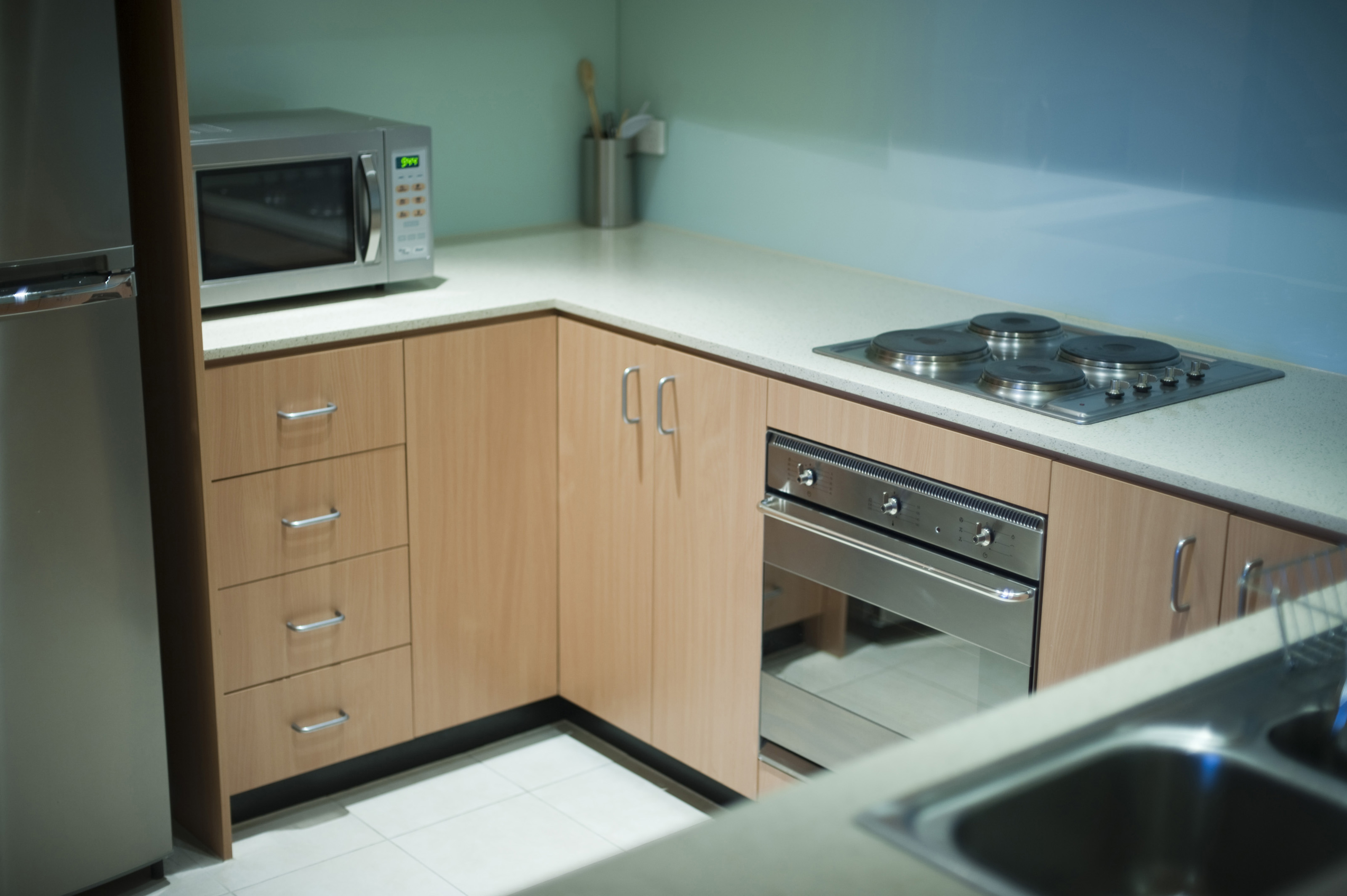 Simple Neat pact modern kitchen with a fridge undercounter stove and hob sink and microwave
