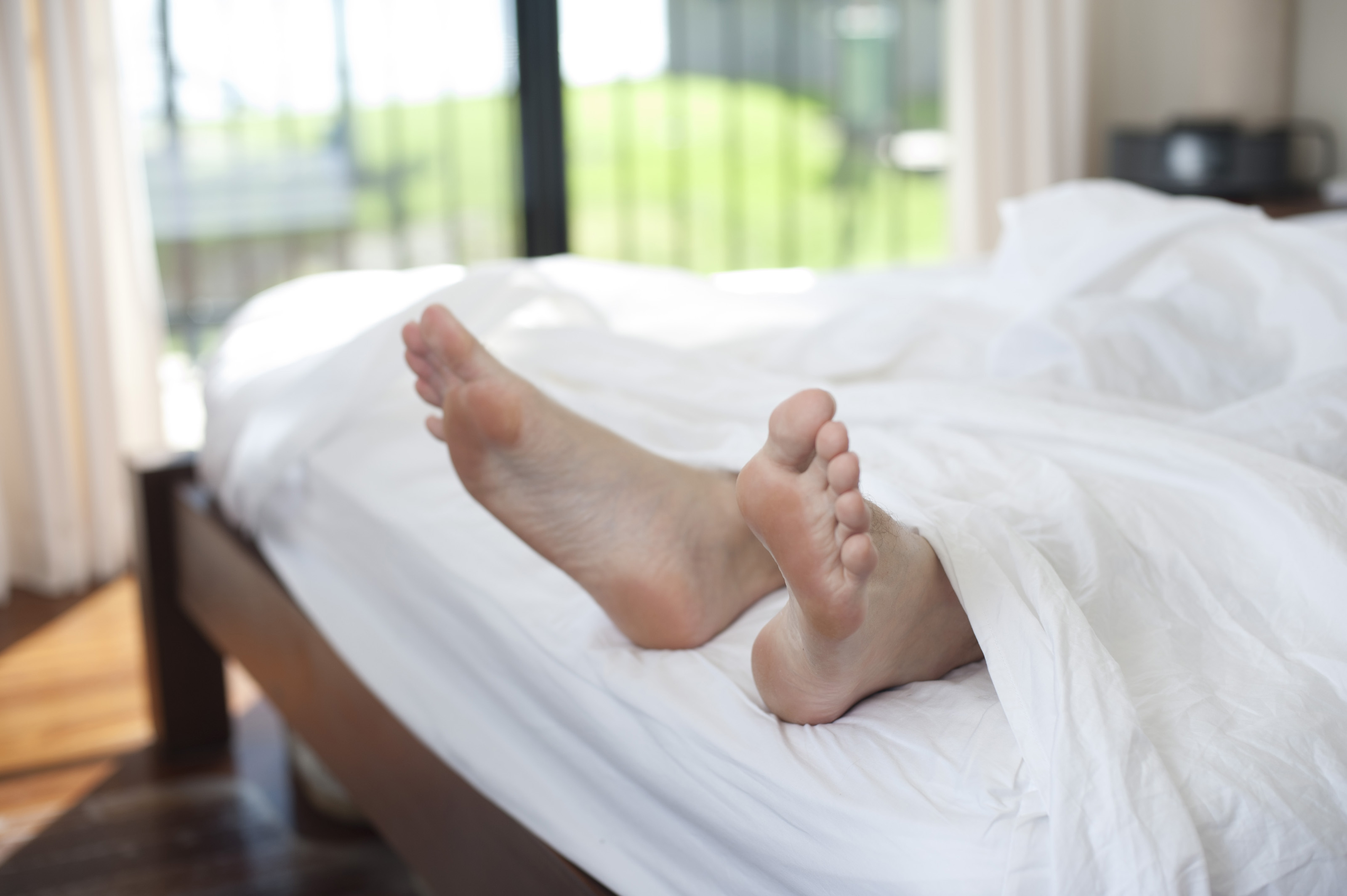 man having a weekend liein in his bed with a view of his feet