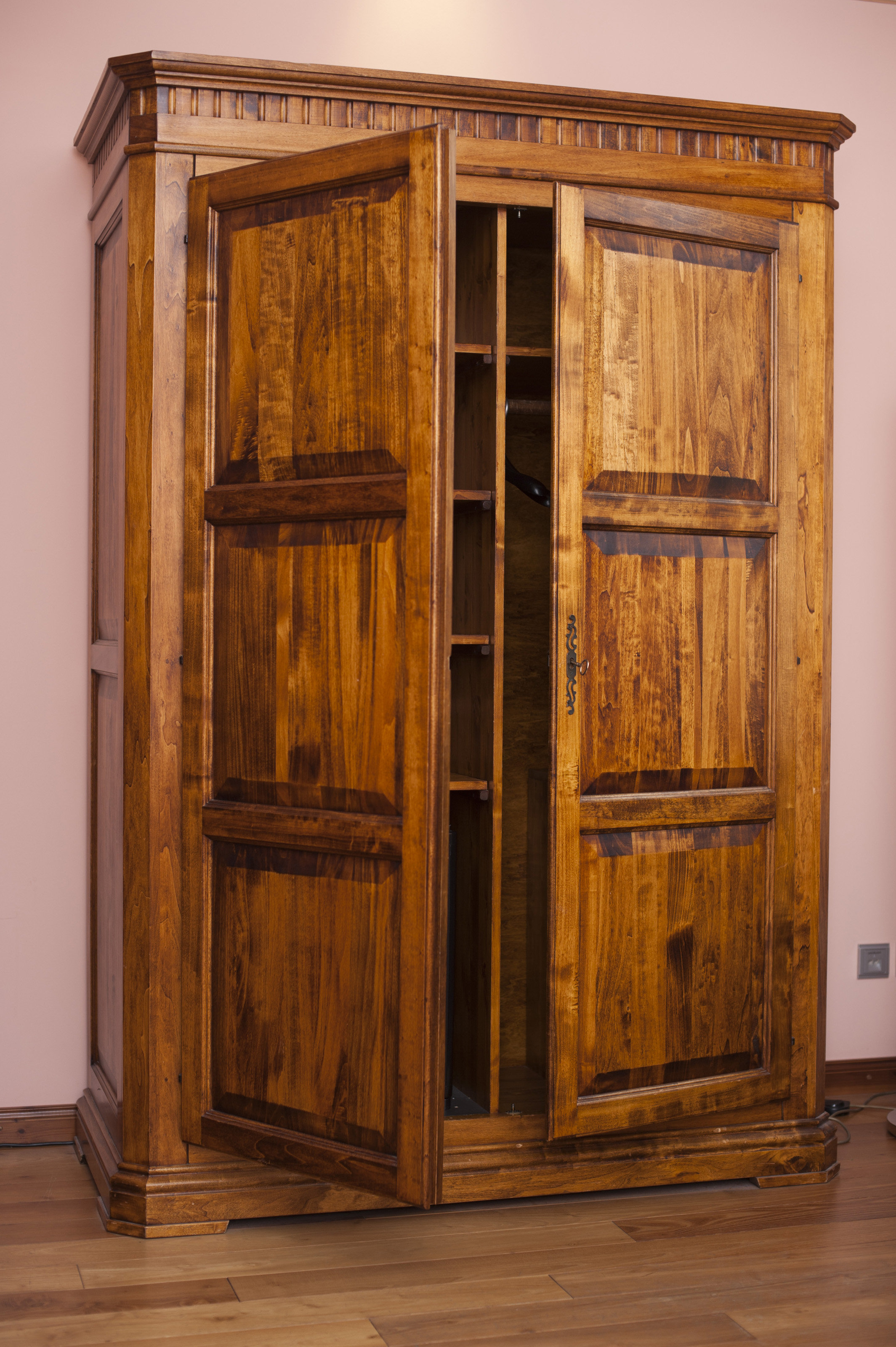 Large Old Rustic Wooden Wardrobe Or Cabinet Used To Store Clothing Standing In A Bedroom With
