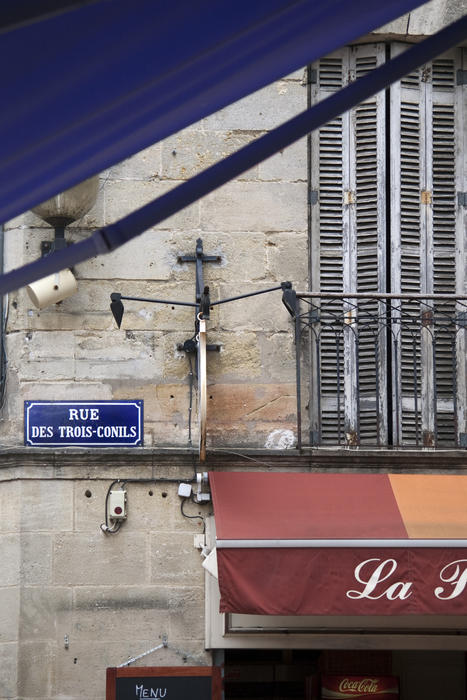details of a french town street, blue enamel street sign, cafe awning, and shuttered windows