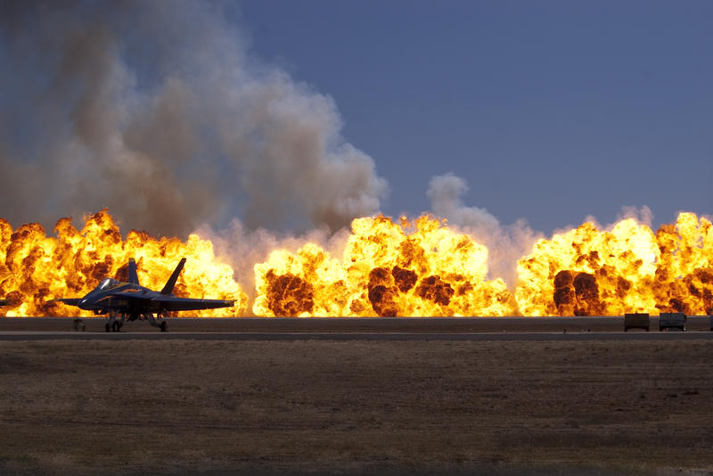 fire balls at an airshow with an FA18 in the foreground