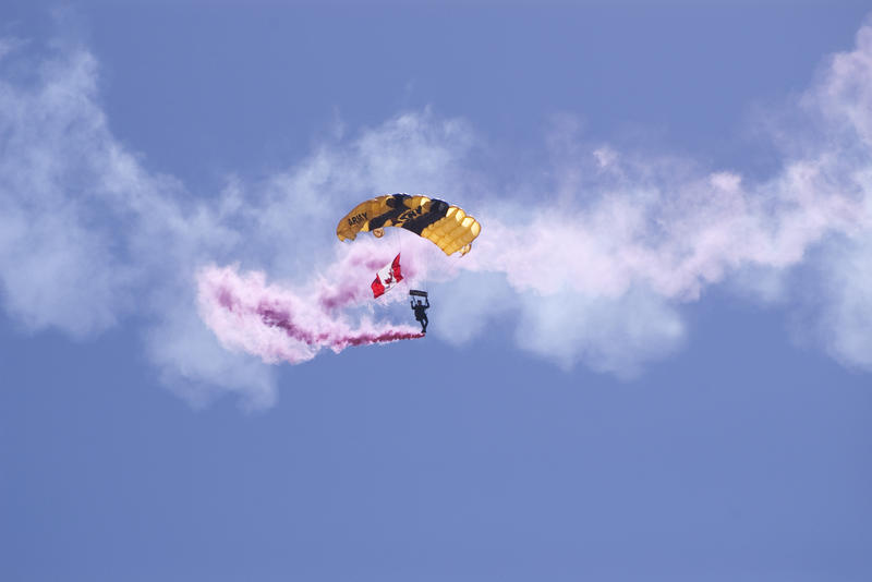a canadian army parachutist gliding down with a trail of pink smoke