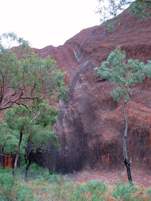 the rare sight of water running down the side of uluru after a passing downpour