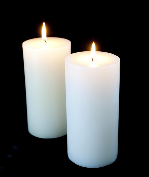 two plain white christmas candles on a black background