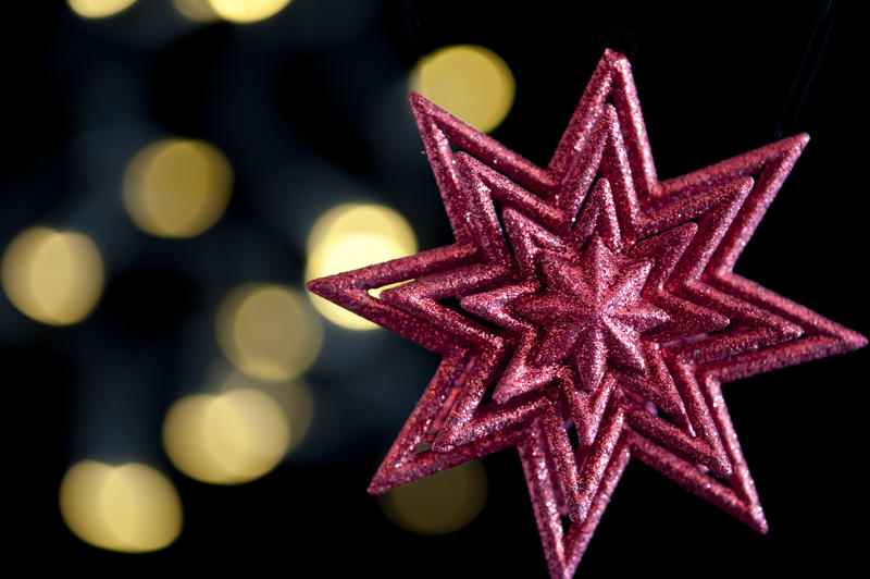 a red christmas star shaped decoration on a background of white defocused christmas lights