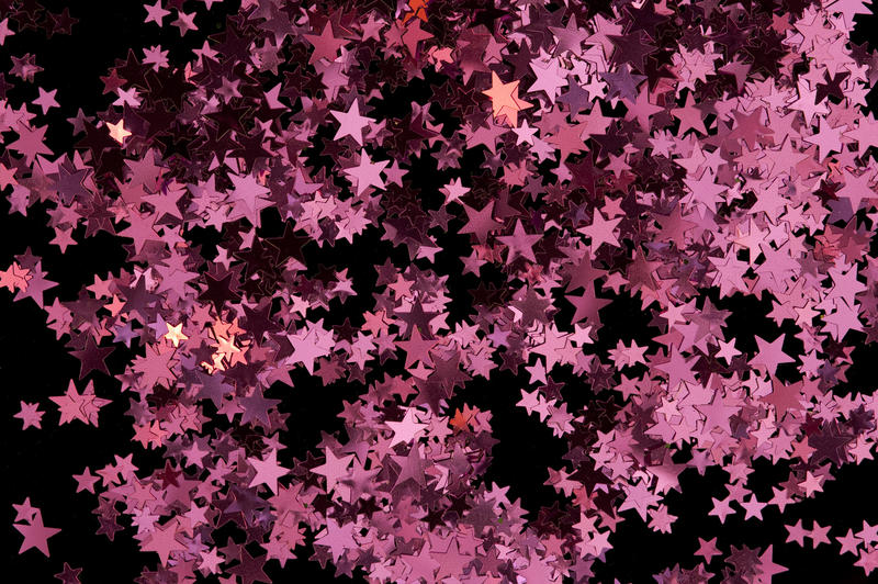 a colorful backdrop of scattered red star shaped confetti