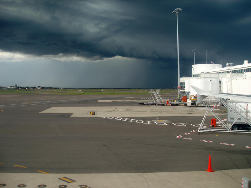 a menacing looking storm cloud over an airport runway