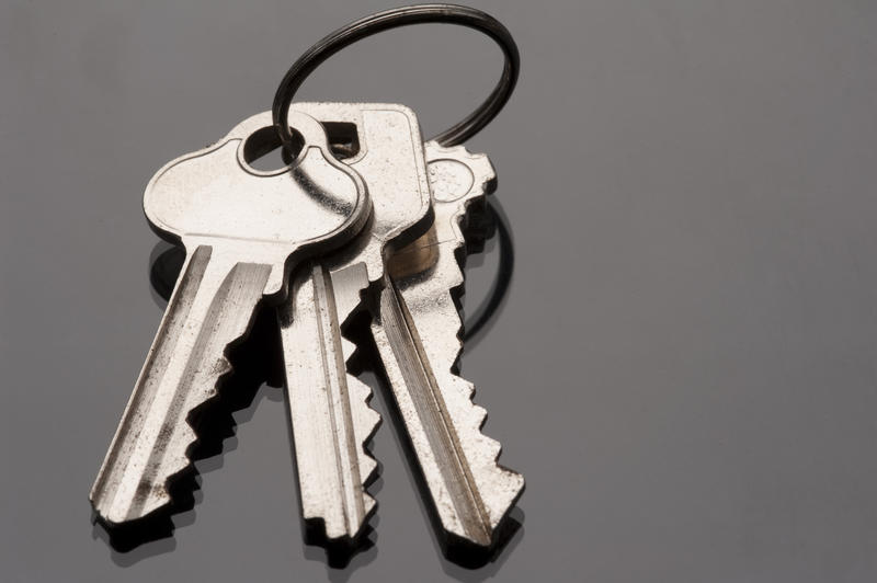 a metal keyring and three keys on a dark surface