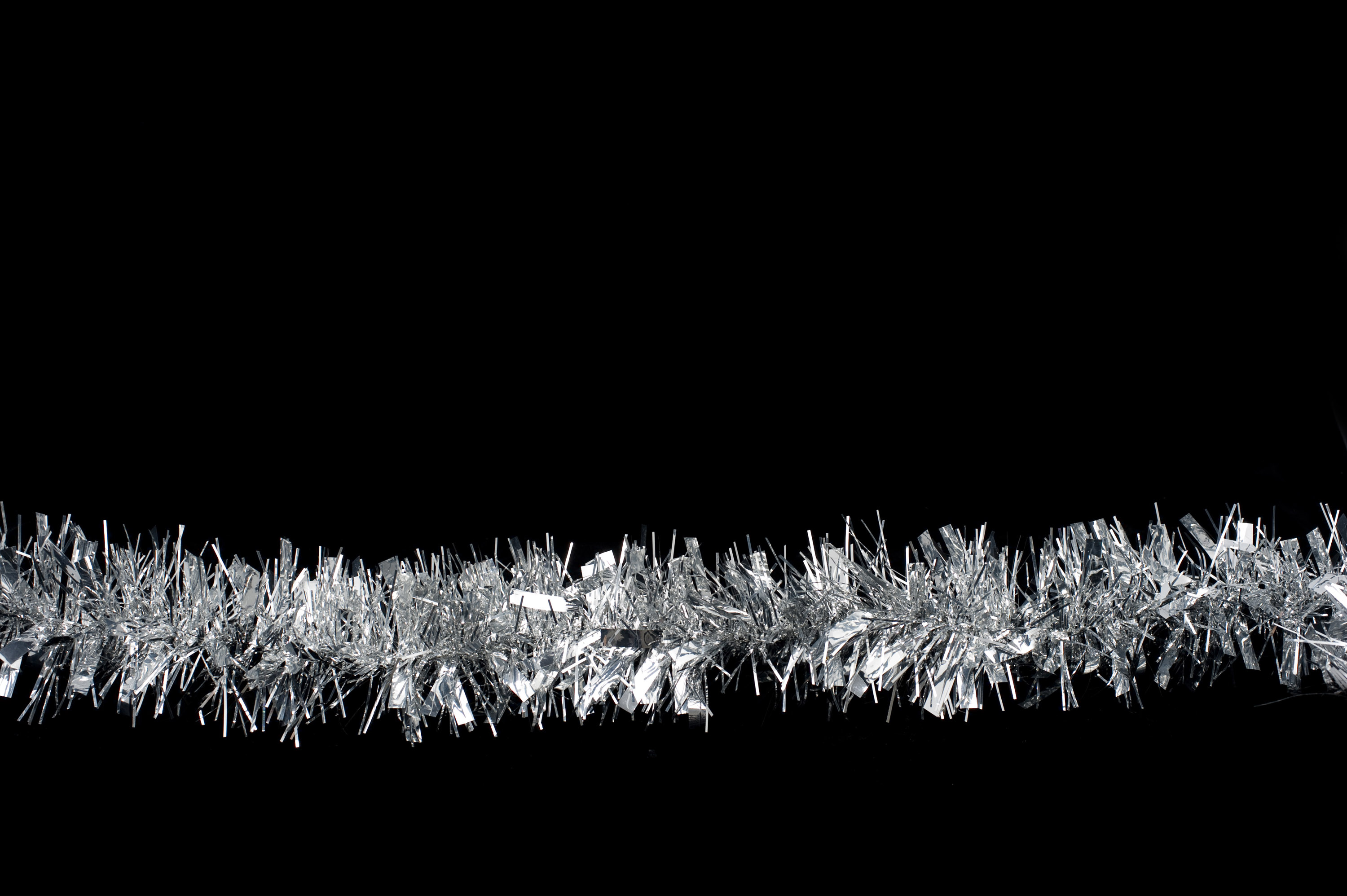 a line of silver christmas tinsel on a plain black background - Black Christmas