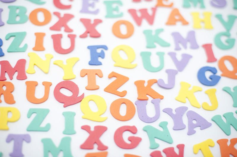 Colourful alphabet background with random scattered uppercase letters on a white surface