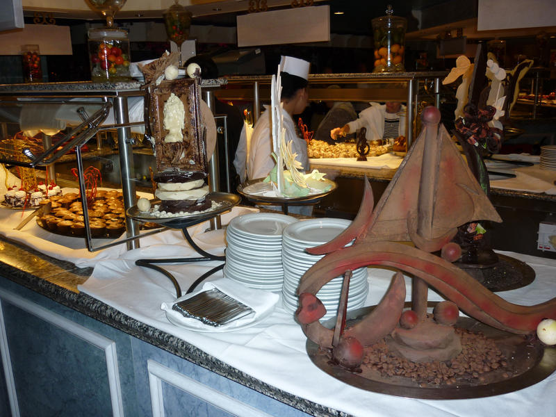 Food buffet table with nautical themed decoration and an assortment of food dishes and serving plates
