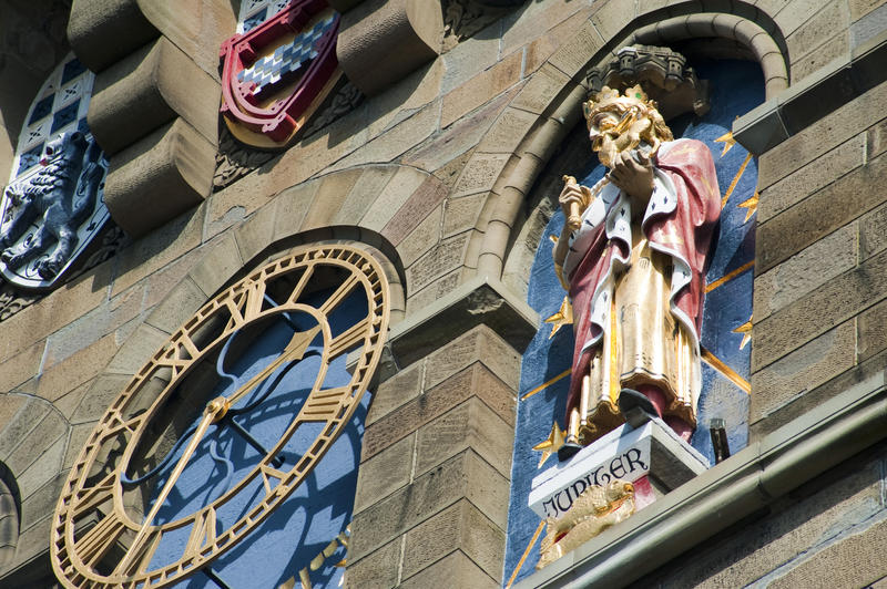 One of the gilded metal clock faces on the clock tower of Cardiff Castle, Wales flanked by sculptures representing the planets