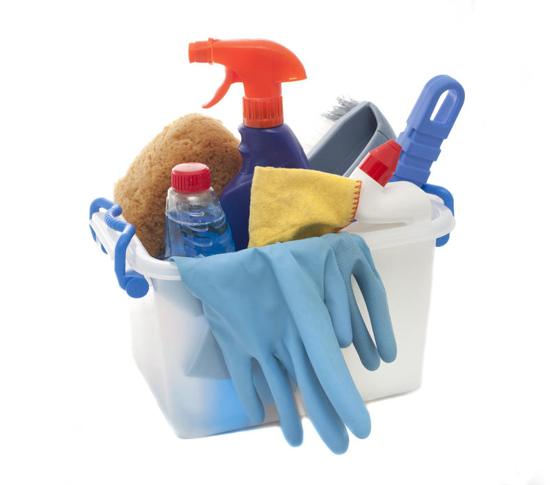 Plastic tub filled with household cleaning products including detergents, a spray bottle, gloves, sponge and cloth to ensure a healthy lifestyle