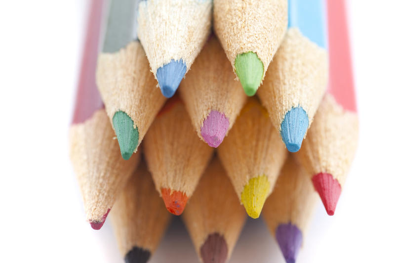 Artistic background of the colourful palette of pencil crayons with a close up view of the sharpened points facing the camera