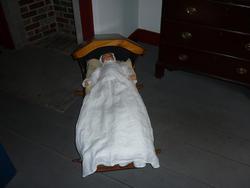 6755   Antique doll lying in a crib