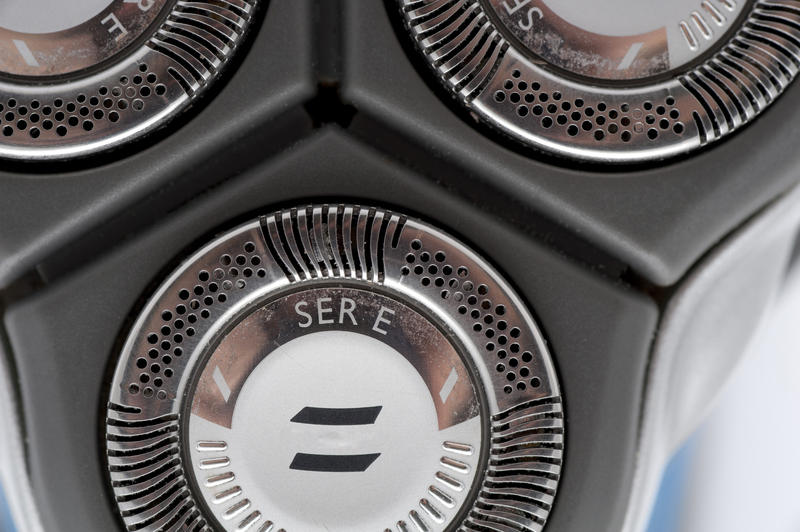 Closeup of one of the three circular stainless steel blades of an electric shaver for trimming facial hair