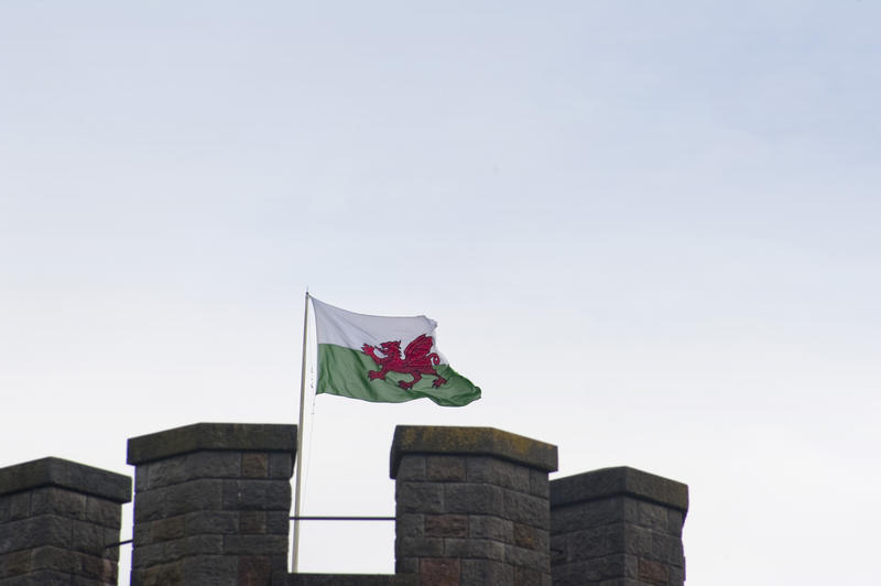 The Welsh Flag , otherwise called Baner Cymru or Y Ddraig Goch, meaning The Red Dragon, flying over the ramparts of a castle in Wales