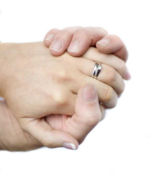 hands of a caucasian couple with hands crasped together and a wedding and engagement rings on display